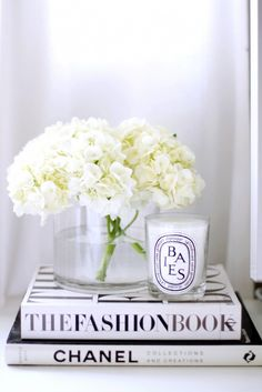 Hydrangeas and candles atop fashion coffee table books.