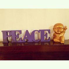 """Baby buda dorado acompañado de palabra corpórea """"Peace"""" violeta"""