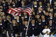 Phelps, a 22-time Olympic medal winning swimmer, waved the flag during the welcoming of the athletes