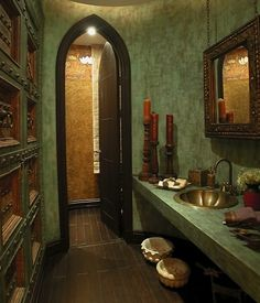 Moroccan style bathroom featuring textured walls, scalloped sink, ornate carved woodwork & a curved peak door frame.