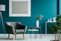 Green armchair against blue wall with silver painting in living room interior with plants Living Room Paint, Living Room Interior, Deco Violet, Modern Radiator Cover, Wall Mounted Storage Shelves, Stair Shelves, Hanging Shelves, Floating Shelves, Green Armchair