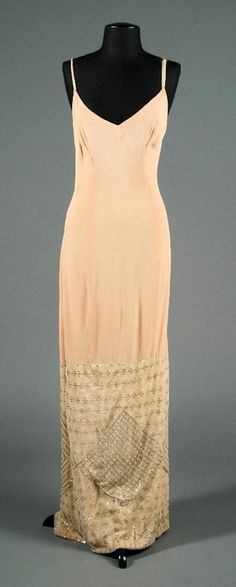 Barbra Streisand Art Deco Style Custom evening dress - 1976 - Peach silk crepe and chiffon net full length gown, spaghetti straps, low cut back, slit at back to approximately knee area. Bottom third comprised of chiffon net encrusted with crafted geometric patterns. This piece was worn by Streisand during promotion of the film A Star Is Born - LiveAuctioneers