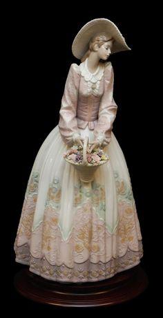 "Lladro ""Spring Courtship"" Porcelain Figure: Lladro Spanish porcelain sculpture depicting a woman holding a basket. Sculpted by Slavador Debon. Glazed finish."