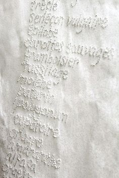 Embroidered French knots of a shopping list in French, on a tea towel. Beautiful - would make a nice shower gift.