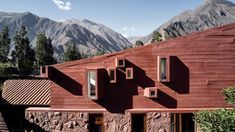 Lima studio Barclay & Crousse has completed this house with reddish stone and concrete walls, and dramatically slanted roofs to echo mountains.