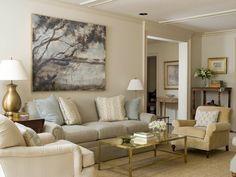 Yellow beige chair, slight butterscotch undertone sisal carpet, green gray sofa and light beige walls.