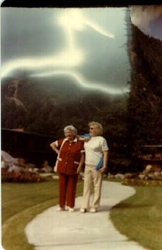 This picture was taken on a warm sunny afternoon in July 1980 at Three Valley Gap which is located 12 miles west of Revelstoke, British Columbia, Canada. The woman and her sister were standing in the motel park with a steep mountain wall behind them. Why is the mountain cut off vertically and what are the strange swirling lights in the sky? The camera was a Balda Folding Roll Film Camera, 120 size Kodacolor, 1/200 of a second at F- 11. The woman and her sister were later found dead.