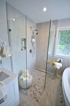 """Beautiful #bathroom #renovation featuring a spacious curbless #shower built with Schluter products including Kerdi waterproofing membrane, Ditra decoupling membrane and Kerdi-Line linear drain.  A freestanding bathtub rests on a bed of flat ground toasted biscuit coloured river pebbles, while the remaining floor is tiled with 6"""" x 36"""" Italian driftwood inspired porcelain tile.  In addition, a dual sink semi-custom bathroom #vanity with full extension soft-closing doors and drawers was installed."""