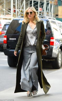 Street style: Kate Hudson looked fashionable in a long green coat and silver and grey ense...