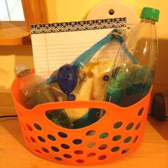 Break bucket for when students are feeling overwhelmed or angry. Contents include an Ispy bag, drawing pad, stress balloon, and distilled water and glitter bottles.
