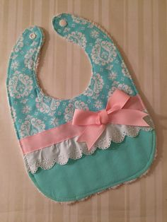 Super Cute Bib - Aqua, Pink & White with Bow   Pre-washed 100% cotton fabric Soft terry cloth on back Measures approximately 11.5 x 8 Grosgrain Ribbon Eyelet lace trim Snap Closure  * Bib is handmade in a smoke-free home.  At My Modern Thread we pride ourselves on creating handmade, one of a kind, modern baby bibs. They are always well-tailored and made of top quality materials. Looking for something in particular? Let us know we will be happy to make that special custom made bib just for...