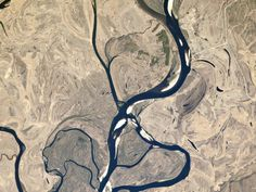 Rivers that flow down a shallow gradient tend to meander, looping back and forth over the terrain. These motions, which take place over decades and centuries, are preserved in patterns visible in the flood plain of the Selemdzha River in Russia. Rocks And Minerals, Geology, Planets, Irrigation, Shallow, Fossils, Rivers, Flow, Russia