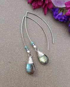 These simple and elegant earrings feature flashy, gray Labradorite drops wrapped with antique brass or silver wire. These sprakly, faceted gems are on long earwires with faceted metal and Czech crystal accents. The earrings are approximately 2.25 long but lightweight. The earwires are