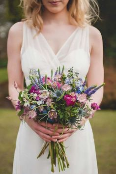 a colorful wildflower wedding bouquet with purple, blue and pink blooms and blue thistles #weddingbouquets
