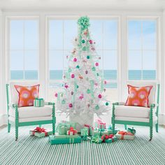 The Frosty Flamingo - Coastal Christmas Trees - Coastal Living | This groovy palette of sea foam, pinks, and corals is full of retro-inspired fun. The white branches of flocked spruce trees like this one make ornaments in hot hues shine. Conceal the stand in a garden planter—we used a patterned, Chippendale-style container. Channel retro cheer with quirky 1940s saucer ornaments, and then balance the kitsch with translucent jade globes. Crown with a large bow. Let the party begin!