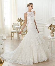 REPIN THIS 2014 Lenix by PRONOVIAS Petit pois tulle wedding dress with rebrodé lace appliqué, ribbon and crystal gemstone embroidery. Bodice with round neck and pronounced armholes with a sheer layer over a sweetheart neckline. The skirt fans out from the hip with two frills, appliqués and a scalloped hem. Stitched satin belt, fastened at the front with a bow.
