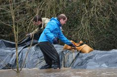 Prince William, Duke of Cambridge builds a dam to help with flood defences around Eton End School on February 14, 2014 in Datchet, United Kingdom...