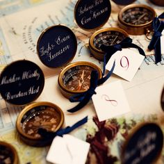 Brides.com: A Traditional Wedding in Chicago, Illinois. Danielle DIY-ed the couple's escort cards: Ivory tags tied to miniature compasses with velvet blue ribbon.