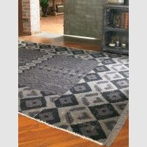 A modern geometric pattern and aged charcoal, hand-knotted wool.