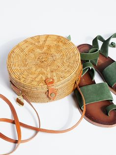Sol Crossbody Bag | Rattan crossbody bag featured in a circular shape.    * Faux leather strap   * Snap closure   * Linen lining   * Interior has a zip pocket