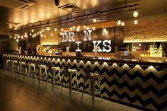 Back bar signage and over bar lighting. Herringbone tile style.