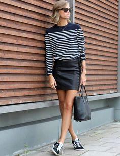 Portée avec un top rayé et une paire de Gazelle, la mini jupe en cuir adopte une allure estivale (TheFashionEaters)