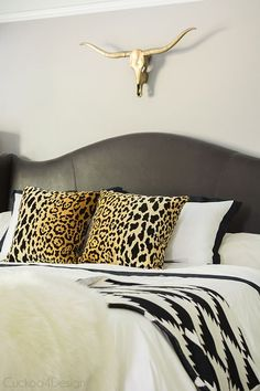neutral black and white bedroom with brass and leopard accents, fur, leather studded wingback bed - Cuckoo4Design