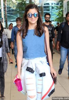Alia Bhatt spotted at the airport wearing a pair of glossy blue round sunglasses, denim crop top and ripped jeans. via Voompla.com