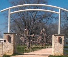 Pretty entrance gate with 4 horses and a dog.