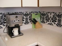 They covered their cabinets in contact paper and used dollar store placemats to create the backsplash pattern.