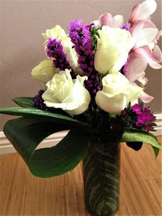 Inspired by winter, white Roses symbolize the softness of snowflakes. Pink Orchids add color and warmth of spring to come, while giving a focus of elegance.The deep purple Liatris spires provide depth to the arrangement. Manipulated greens and succulents gives this bouquet a beautiful contemporary feel.