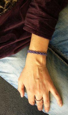 Ein geknüpftes **Armband** in sattem Lila mit eingearbeiteten silberfarbenen Perlchen.  Es ist mit Schiebeverschluss größenverstellbar und lässt sich somit individuell anpassen. Material: S-Lon...