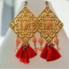 Aretes en oro gold filled, cristales, rosas en resina y borlas en tono rosa.
