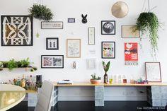 Parede galeria reúne quadros, pôsteres, plantas e peças de porcelana, como a máscara de coelho.