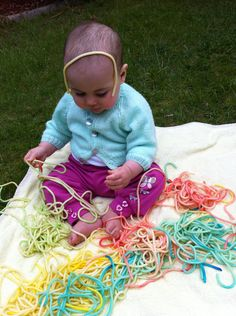 Baby playing with cooked and coloured pasta. Great sensory activity with simple instructions on how to make it.
