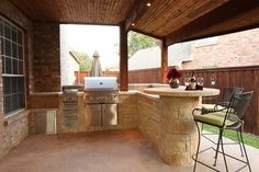 Outdoor kitchen with BBQ, storage drawers, and bar table. By Outdoor Signature in Argyle, TX