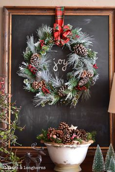 Gorgeous Christmas wreath hung against a chalkboard.