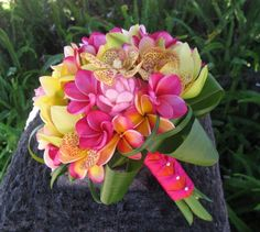 Plumerias, Cymbidiums, Mokara Orchids & Pink Gingers collared with Lily Grass & Ti ~ Finished with Orange and Hot Pink Ribbon and Pearl Pin Accents... beautiful!