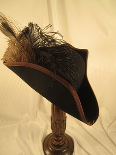 HALLOWEEN PIRATE HAT DESCRIPTION  BLACK FELT PIRATE HAT WITH BROWN TRIM EDGE, PEACOCK FEATHER, OSTRICH FEATHERS. SIZE - Medium - WILL FIT HEADS THAT