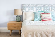 A cheerful and colorful bedroom with midcentury side table and patterned headboard