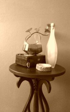 Decorando esquinitas reutilizando materiales: - La base de la planta es un teléfono antiguo en su caja, que por el momento no tiene otro uso.  - Una botella de licor que tiene una linda forma. Agrando plantas y toque rústico con el cenicero de tronco.