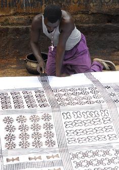 Anthony Boakye uses a comb to mark parallel lines on an adinkra cloth in Ntonso…