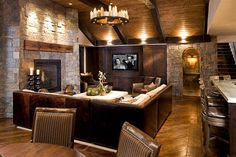 Natural stone and reclaimed timber shape the rustic living room [Design: John Kraemer & Sons]