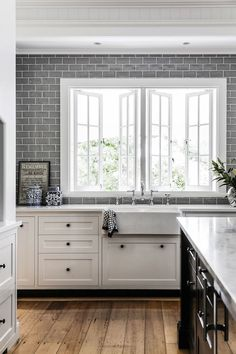 This beautiful redesigned white Queenslander home has a Hamptons style about it … so fresh, classic and light-filled. Love the marble counters, grey hand-glazed Spanish tiles and wood floors of the kitchen, and the Spanish subway tiles and Pietra marble floor tiles in the bathroom. This stylish home was redesigned by Trebilcock & Associates Architects, photos by …
