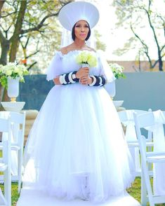 "How beautiful is incorporating Zulu Hat ""Isicholo"" and beaded bangles in her white wedding gown. Sepedi Traditional Dresses, South African Traditional Dresses, African Traditional Wedding Dress, South African Wedding Dress, African Wedding Attire, White Wedding Gowns, Top Wedding Dresses, Zulu Wedding, Diy Wedding"