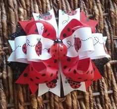 Handmade hair bow! All my bows are starched to hold shape and hand sewn. This bow is about 4.5 inches wide with a cute lady bug in the center