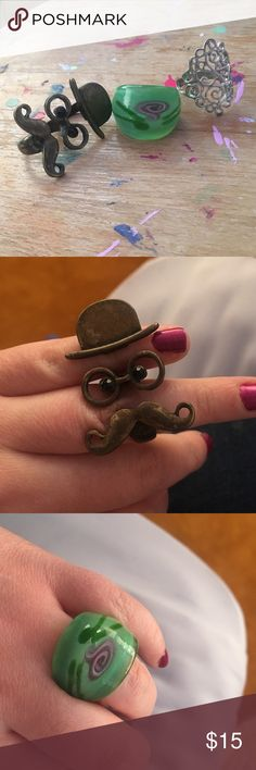 3 ring bundle! :) Cute rings for 15$! One is a face with a mustache, nose and a hat! The eyes look like they are black diamonds. Next is a green and blown glass ring with a little flower on it, then next is a sterling silver ring with nice swirls all around it ! Forever 21 Jewelry Rings
