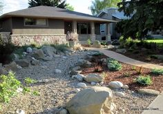 Xeriscaping large rocks mixed with plants and mulch