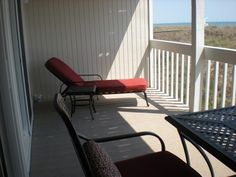 Chaise lounge and table on carpeted balcony deck