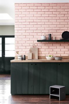 Pink brick backsplash and green cabinets